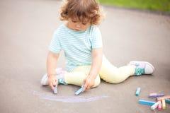 Disegno sveglio della ragazza del bambino con il pezzo di gesso di colore Fotografia Stock