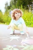 Disegno sveglio della ragazza del bambino con il pezzo di gesso di colore Fotografia Stock Libera da Diritti