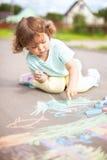 Disegno sveglio della ragazza del bambino con il pezzo di gesso di colore Immagine Stock Libera da Diritti