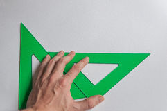 Disegno tecnico, uomo che tiene squadra a triangolo immagini stock libere da diritti