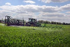 Diserbanti di spruzzatura del giacimento di grano dell'agricoltore Fotografia Stock