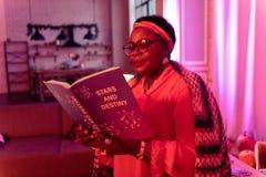 Diseur de bonne aventure dodu d'afro-américain dans l'eyewear lisant un livre sur l'astrologie photographie stock