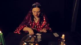 Diseur de bonne aventure gitan à la table par des cartes de merveilles de lueur d'une bougie Le plan moyen clips vidéos