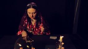 Diseur de bonne aventure gitan à la table par des merveilles de lueur d'une bougie sur les pierres blanches clips vidéos