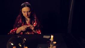 Diseur de bonne aventure gitan à la table par des merveilles de lueur d'une bougie sur les pierres blanches banque de vidéos