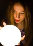 Diseur de bonne aventure roux magnifique tenant la boule de cristal la belle femme essaye d'examiner l'avenir images libres de droits