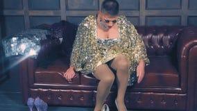 Disfraz-diva El concepto de travestidos de la demostración El actor del hombre da vuelta en una mujer él pone la ropa del ` s de  almacen de video