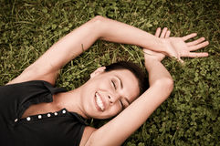 Disfrutando de la vida - mujer que miente en hierba Foto de archivo