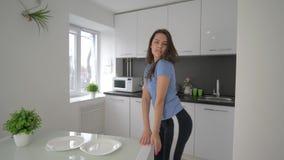 Disfrutando de soledad, feliz femenino divirtiéndose y canta con los platos en manos en la cocina en casa en fin de semana almacen de video