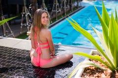 Disfrutar de bronceado Mujer bastante joven en el bikini que se sienta cerca de piscina Fotos de archivo