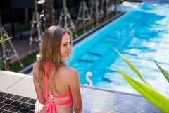 Disfrutar de bronceado Mujer bastante joven en el bikini que se sienta cerca de piscina Fotografía de archivo libre de regalías