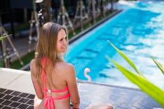 Disfrutar de bronceado Mujer bastante joven en el bikini que se sienta cerca de piscina Fotos de archivo libres de regalías