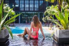 Disfrutar de bronceado Mujer bastante joven en el bikini que se sienta cerca de piscina Imagenes de archivo