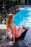 Disfrutar de bronceado Mujer bastante joven en el bikini que se sienta cerca de piscina Foto de archivo libre de regalías