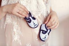 Disfrutar de la vida futura Mujer embarazada que lleva a cabo pequeños botines del bebé en su vientre, primer foto de archivo