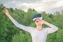 Disfrutar de nueva tecnología Muchacha bonita en auriculares de la realidad virtual Juego lindo de la muchacha en el ambiente sim imagenes de archivo
