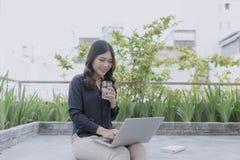 Disfrutar de tiempo agradable en el aire fresco Mujer joven hermosa que trabaja en su ordenador portátil y que sonríe mientras qu fotos de archivo