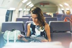 Disfrutar de viaje Mujer bonita joven que viaja por el tren que se sienta cerca de la ventana usando smartphone y que mira el map fotografía de archivo