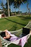 Disfrutar de vida mientras que trabaja en la playa Imagen de archivo libre de regalías
