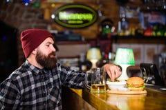 Disfrute de la comida en pub Alto bocado de la caloría El hombre barbudo del inconformista brutal se sienta en el contador de la  imagen de archivo libre de regalías