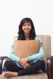 Adolescente feliz aislado que sonríe a la cámara y que sostiene su almohada en casa Imagen de archivo libre de regalías