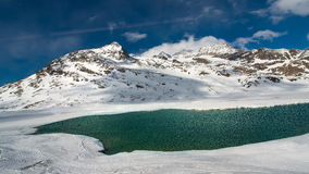 Disgelo del ghiaccio in un paesaggio dell'alta montagna con un lago Fotografia Stock Libera da Diritti
