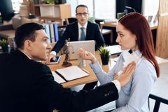 Disgruntled adult man pokes torn marriage contract into red-haired woman in divorce lawyer`s office. stock images