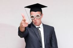 Graduate student. Disgruntled and arrogant graduate student in the cap isolated on gray background. Education concept stock photo