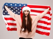 A disgruntled girl in a warm sweater and has a Christmas cap holding a American flag. A disgruntled young girl with long dark hair, of European appearance, is Royalty Free Stock Photo