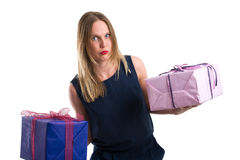 Disgruntled looking woman carrying heavy gift packages Stock Images