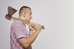 Disgruntled man with an ax on his shoulder. White background royalty free stock image