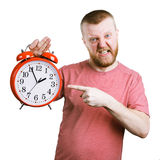 Disgruntled man holding a big alarm clock Royalty Free Stock Photo