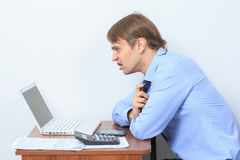 Disgruntled manager at his desk. On a light background Royalty Free Stock Photography