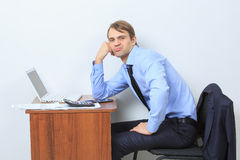 Disgruntled manager at his desk. Looking at the camera Stock Photos