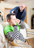 Disgruntled men at home. Two adult men having quarrel at home Royalty Free Stock Image