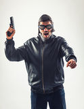 Disguised angry man holding a gun threatening Stock Image