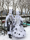 Disguised Couple. Annecy, France, February 23, 2013: Couple disguised in a beautiful white costume posing near a canal in Annecy. France,  during a Venetian Stock Photo