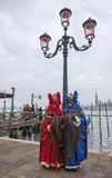 Disguised Couple. Venice, Italy- February 19th, 2012: Two persons disguised in venetian costumes posing near a street light pole near a dock of gondolas during Royalty Free Stock Image