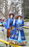 Disguised Couple. Annecy, France, February 23, 2013: Couple disguised in beautiful costumes posing near the lake in Annecy, France,  during a Venetian Carnival Royalty Free Stock Photos
