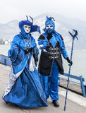 Disguised Couple. Annecy, France, February 23, 2013: Couple disguised in beautiful costumes posing near the lake in Annecy, France,  during a Venetian Carnival Royalty Free Stock Images