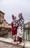 Disguised Couple. Annecy,France-March 15,2014:A couple disguised poses on a bridge during the Annecy Venetian Carnival. Yearly in Annecy ,France is held a Royalty Free Stock Photo