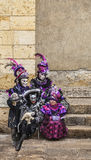 Disguised Family. Annecy,France-March 15,2014:Four disguised people sitting on stones steps during the Annecy Venetian Carnival. Yearly in Annecy ,France is held Stock Images
