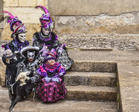 Disguised Family. Annecy,France-March 15,2014:Four disguised people sitting on stones steps during the Annecy Venetian Carnival. Yearly in Annecy ,France is held Royalty Free Stock Photo
