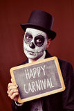 Disguised man shows chalkboard with the text happy carnival Stock Photos