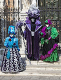 Disguised People. Venice, Italy- February 18th, 2012: A group of three disguised people posing in front of a traditional building during the Venice Carnival days Royalty Free Stock Photo