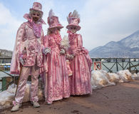 Disguised People. Annecy, France- February 23, 2013: A group of three people disguised in beautiful pink costumes pose near the Annecy Lake during a Venetian Stock Photography