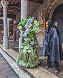 Disguised People. Venice, Italy-February 19, 2012: A person disguised in a beautiful green Venetian costume poses near a person disguised in a ghost during the Royalty Free Stock Image