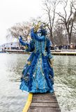 Disguised Person - Annecy Venetian Carnival 2013. Annecy, France, February 23, 2013: Disguised person posing on a pier on Annecy Lake, during a Venetian Carnival Royalty Free Stock Photo