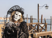 Disguised Woman. Venice, Italy-February 18,2012: Portrait of a woman wearing a beautiful specific costume near the gondola's dock in San Marco Square in venice Stock Photography
