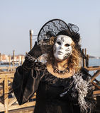Disguised Woman. Venice, Italy-February 18,2012: Portrait of a woman wearing a beautiful specific costume near the gondola's dock in San Marco Square in venice Royalty Free Stock Photos